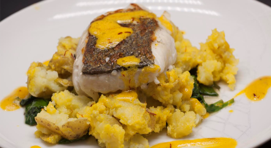 Hake with crushed baby potatoes, buttered spinach and a saffron vinaigrette